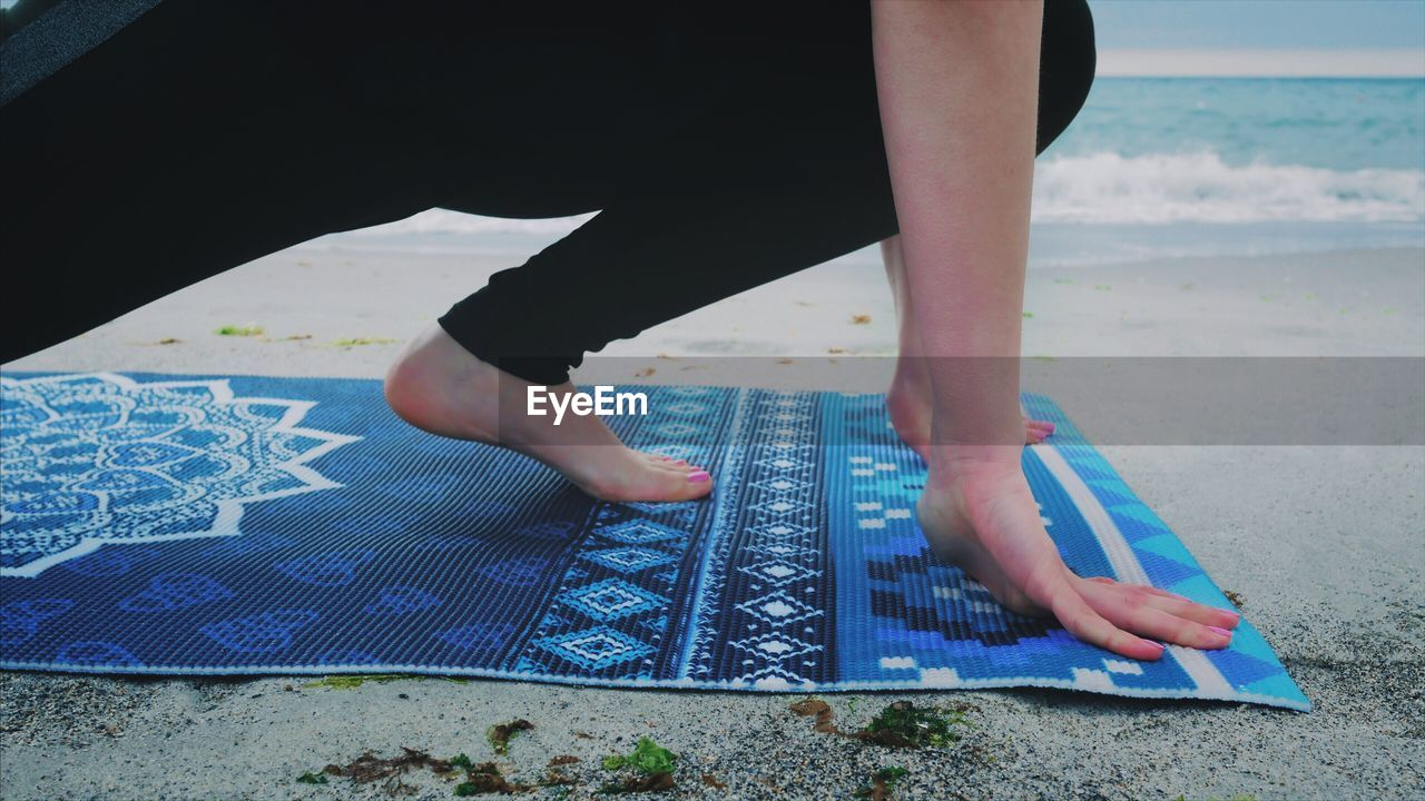 Low Section Of Woman Exercising At Beach
