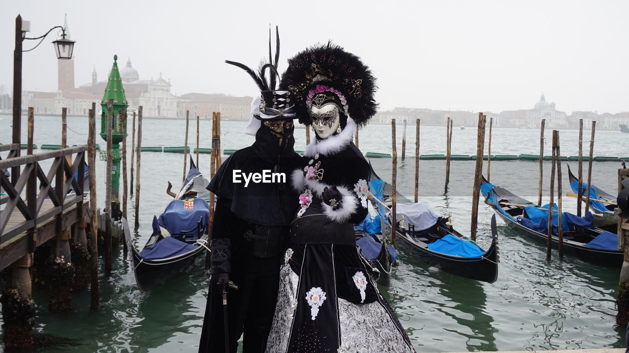 transportation, nautical vessel, mode of transport, gondola - traditional boat, canal, building exterior, travel destinations, outdoors, gondola, day, water, architecture, real people, built structure, wooden post, moored, venetian mask, animal themes, mammal, one person, sky