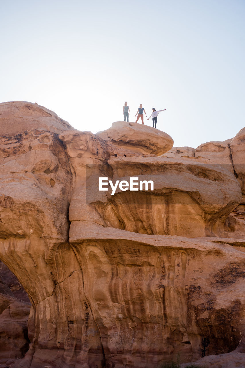 LOW ANGLE VIEW OF PEOPLE ON ROCKS