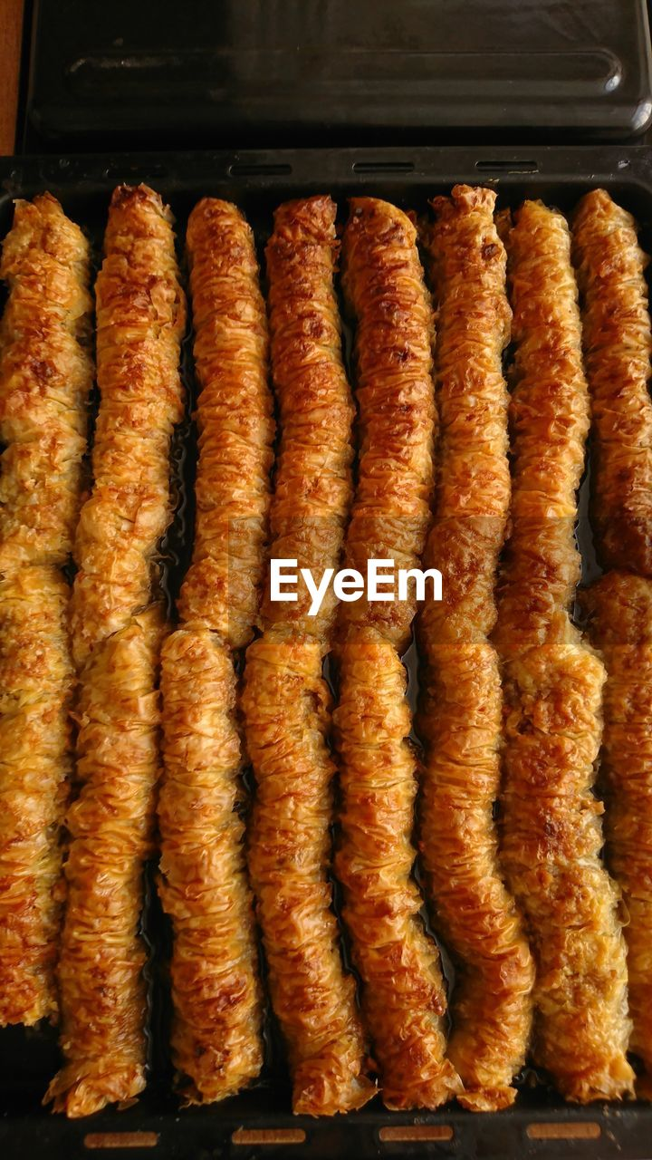 food, food and drink, freshness, meat, still life, indoors, no people, sausage, ready-to-eat, unhealthy eating, close-up, side by side, high angle view, in a row, processed meat, fried, indulgence, fast food, orange color, snack, hot dog