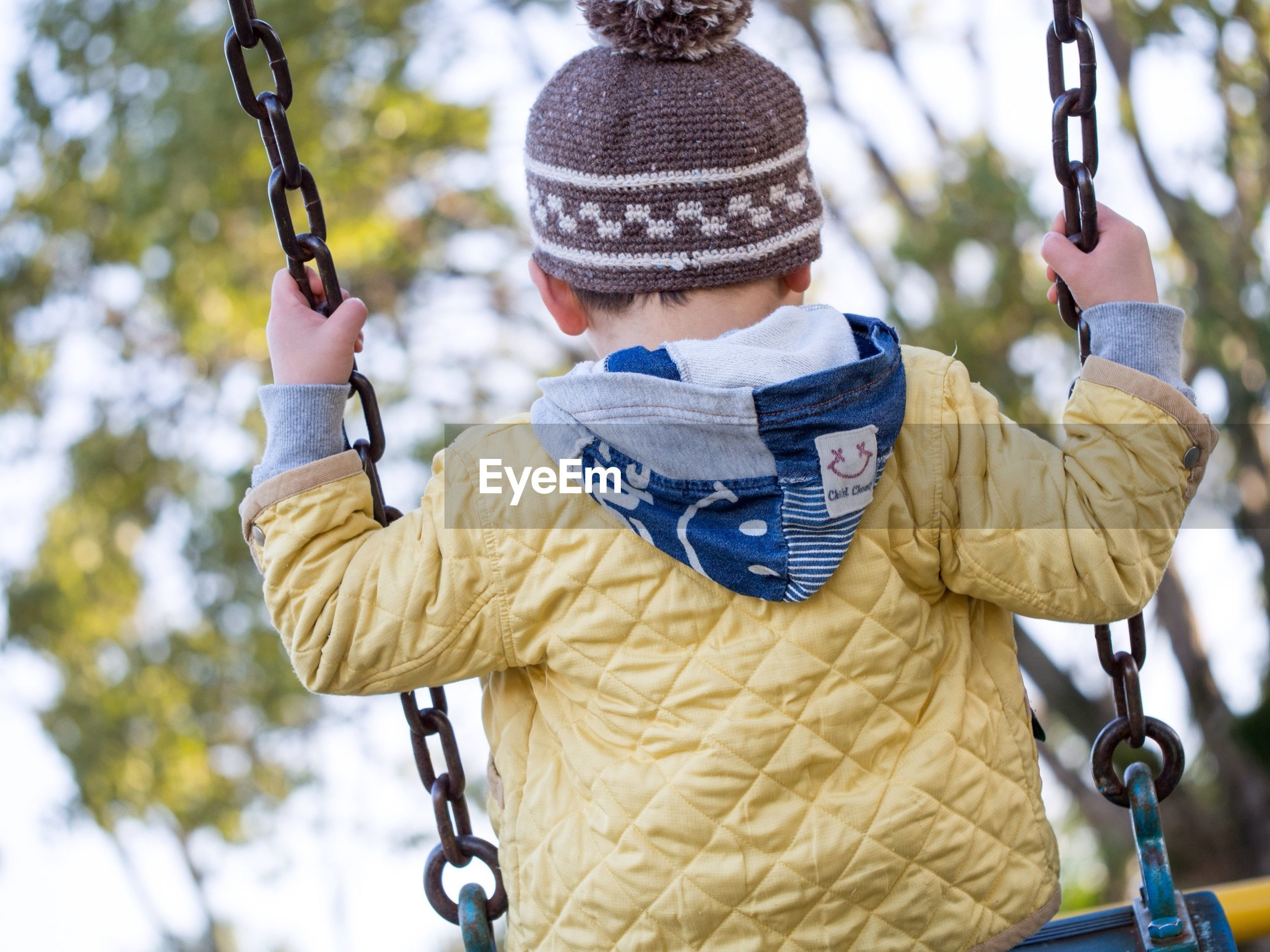 focus on foreground, lifestyles, leisure activity, childhood, casual clothing, holding, full length, day, tree, outdoors, hat, boys, park - man made space, rear view, elementary age, metal, front view, standing
