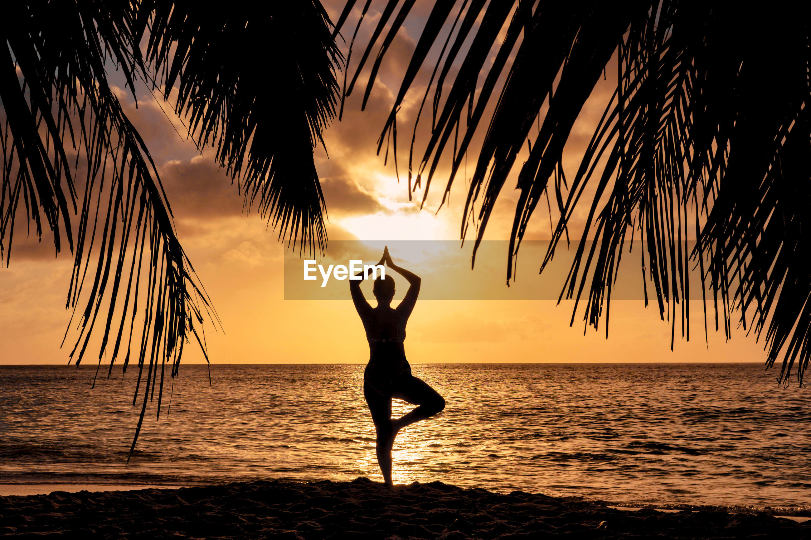 Sunset silhouette of a woman doing yoga on beach.