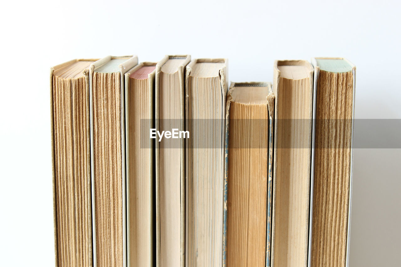 Close-Up Of Old Books Arranged Side By Side Against White Background