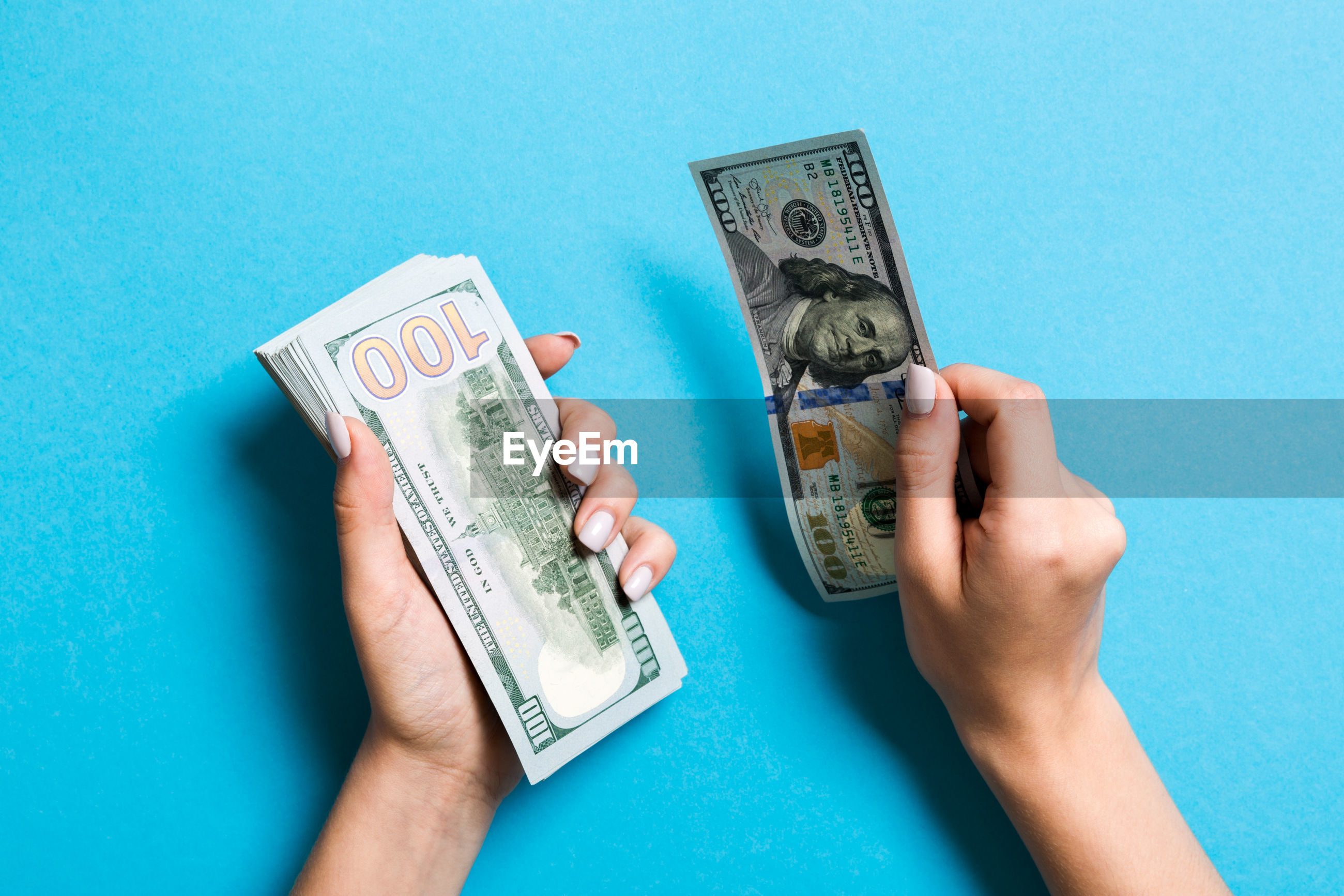 Close-up of hands holding paper currency over blue background