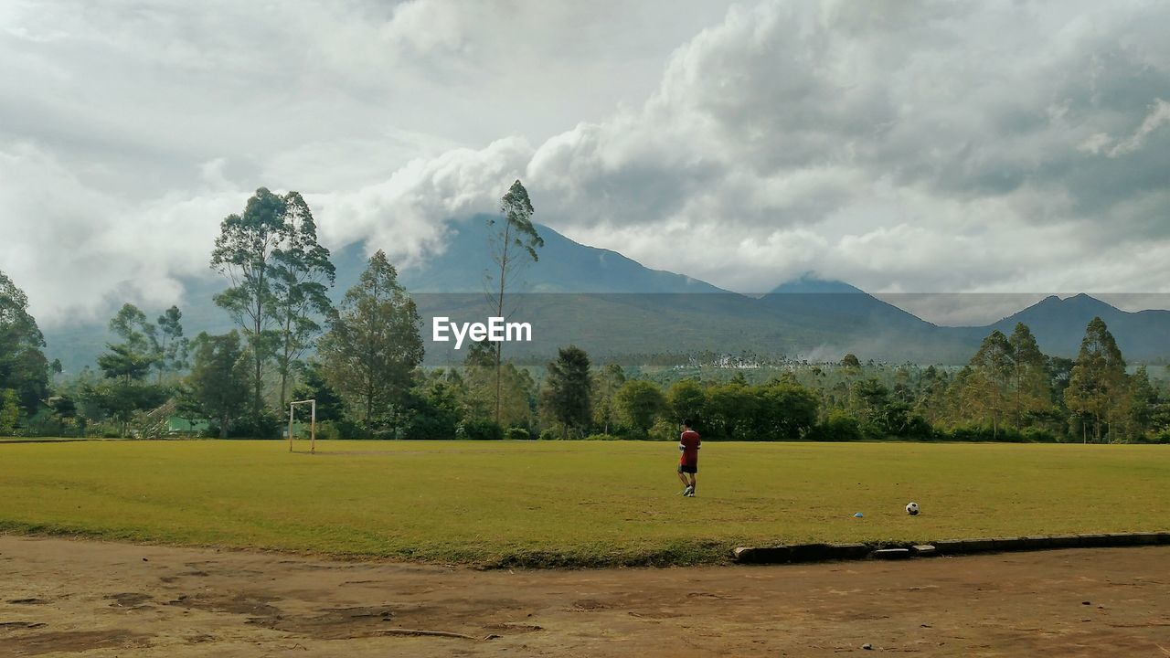 Man playing soccer on field against mountains