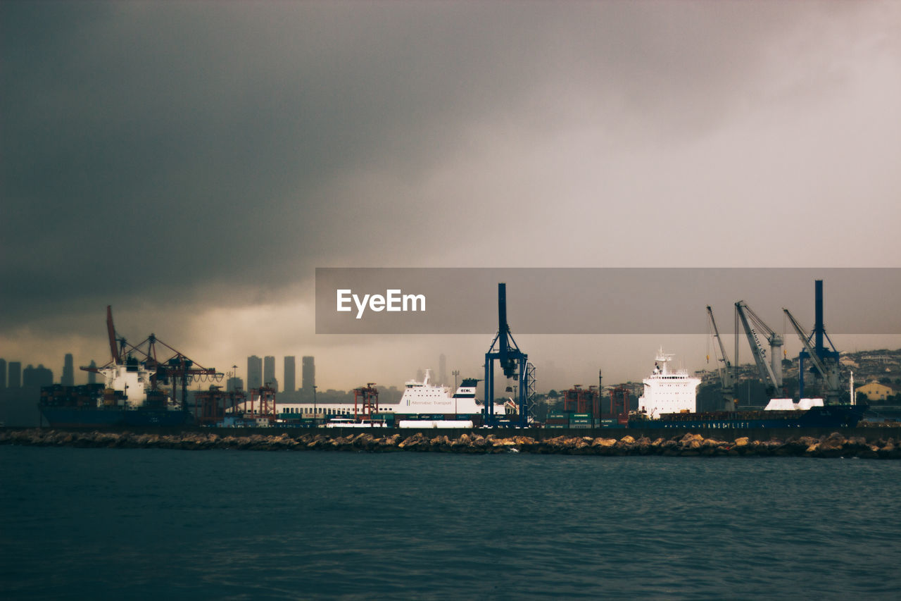 sky, waterfront, commercial dock, crane - construction machinery, no people, building exterior, industry, water, architecture, shipping, sea, nautical vessel, freight transportation, outdoors, harbor, built structure, crane, cloud - sky, ship, factory, city, nature, day, cityscape, skyscraper, shipyard, beauty in nature