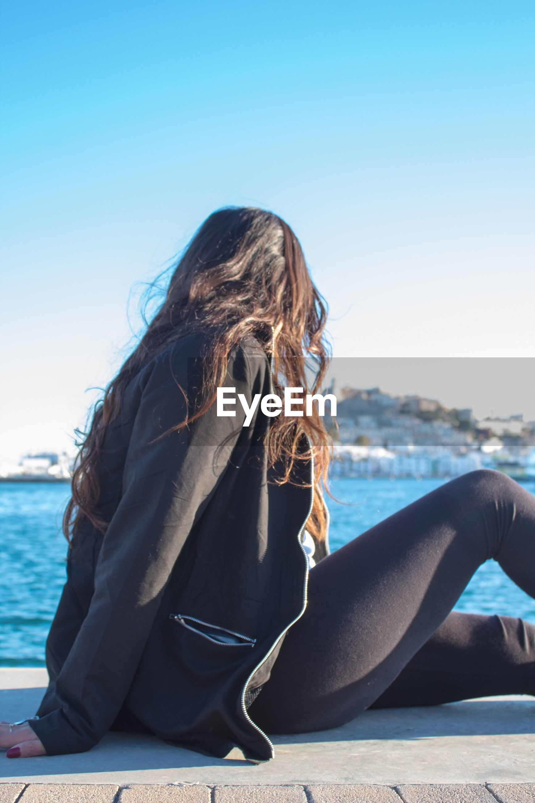 Woman sitting against sea in city