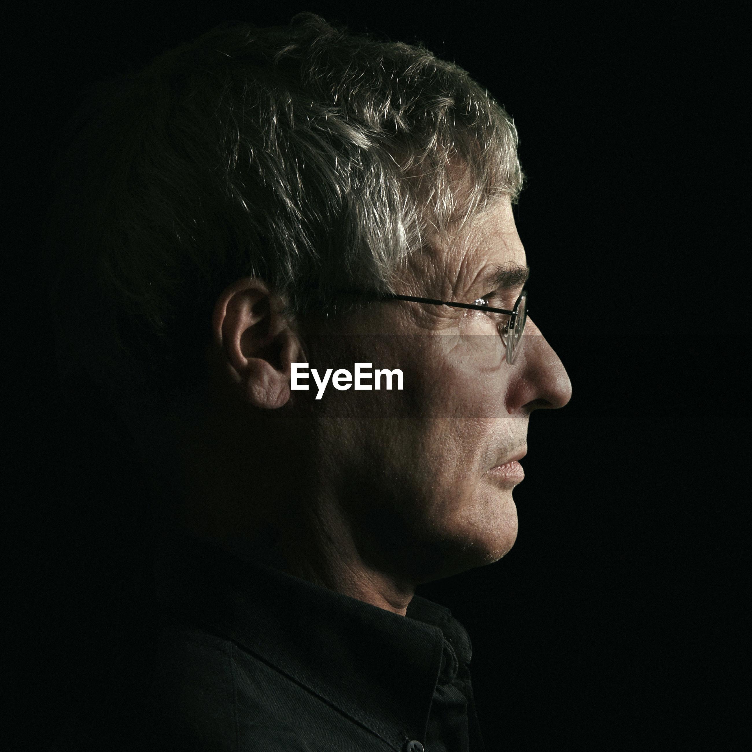 Side view of man wearing eyeglasses against black background