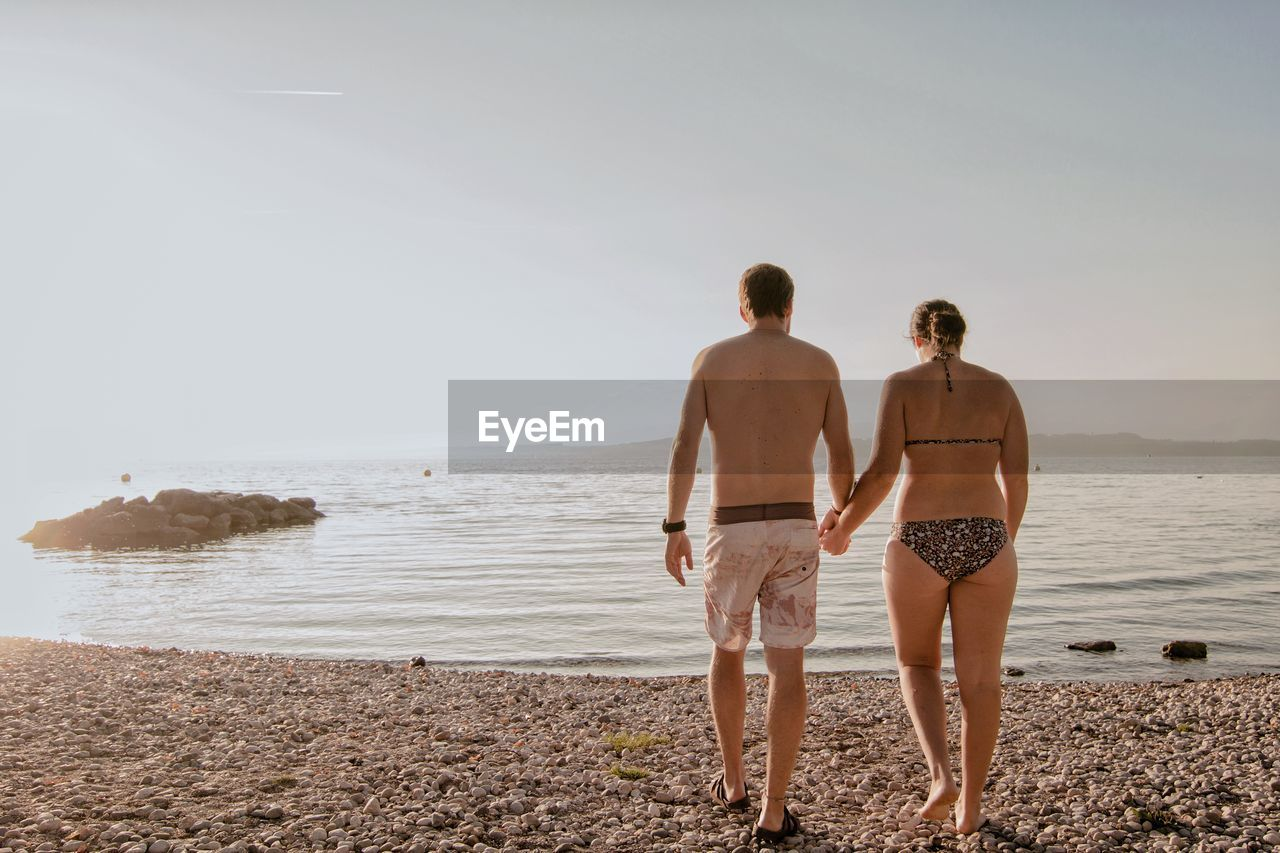 water, two people, togetherness, sea, standing, beach, sky, couple - relationship, men, land, bonding, real people, love, nature, leisure activity, heterosexual couple, copy space, full length, shirtless, positive emotion