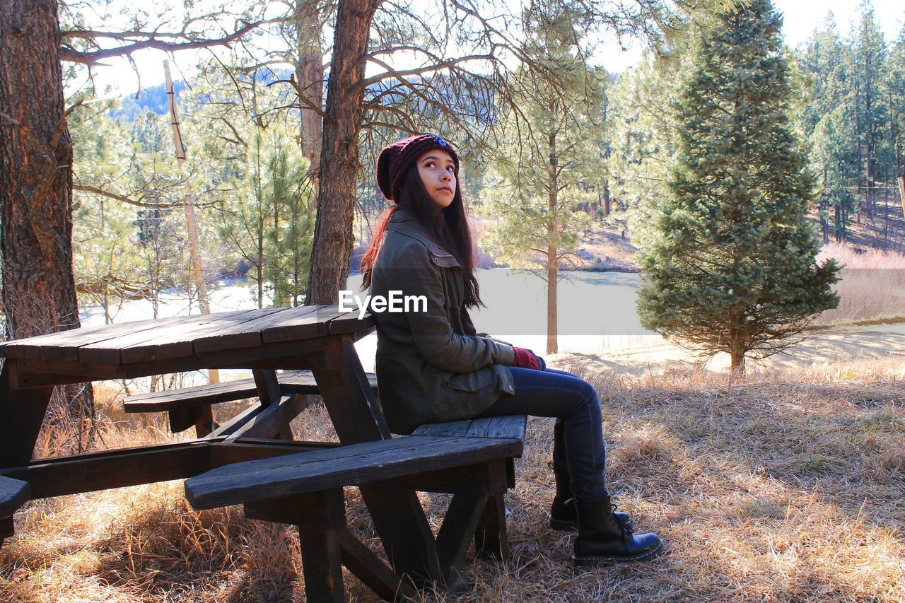Full length of young woman sitting on picnic bench at park