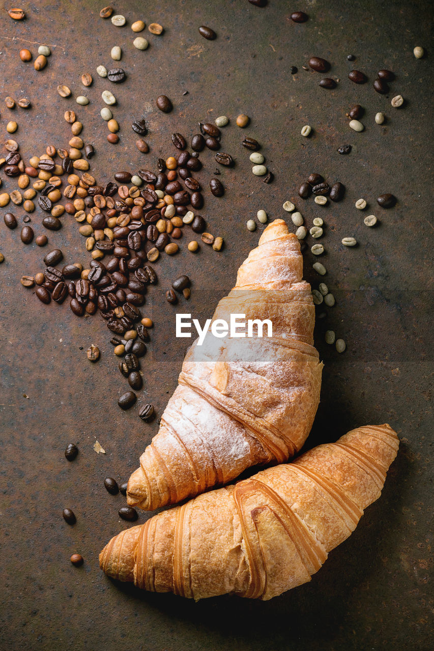 Directly Above View Of Croissants With Coffee Beans On Table