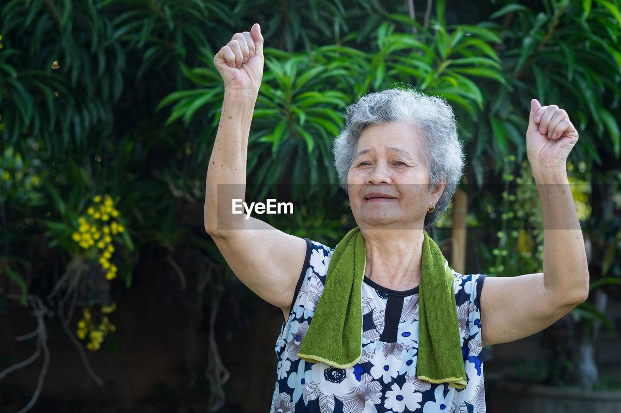 Portrait of elderly woman exercises in garden.