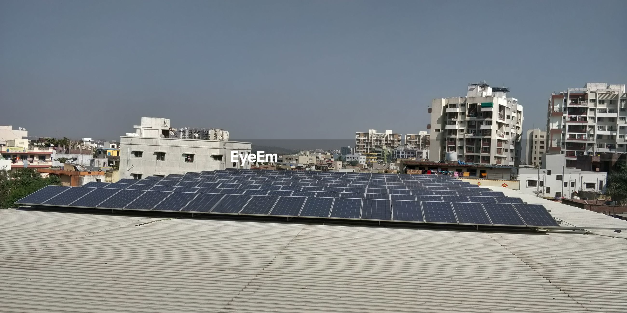 Solar panels on buildings against sky in city