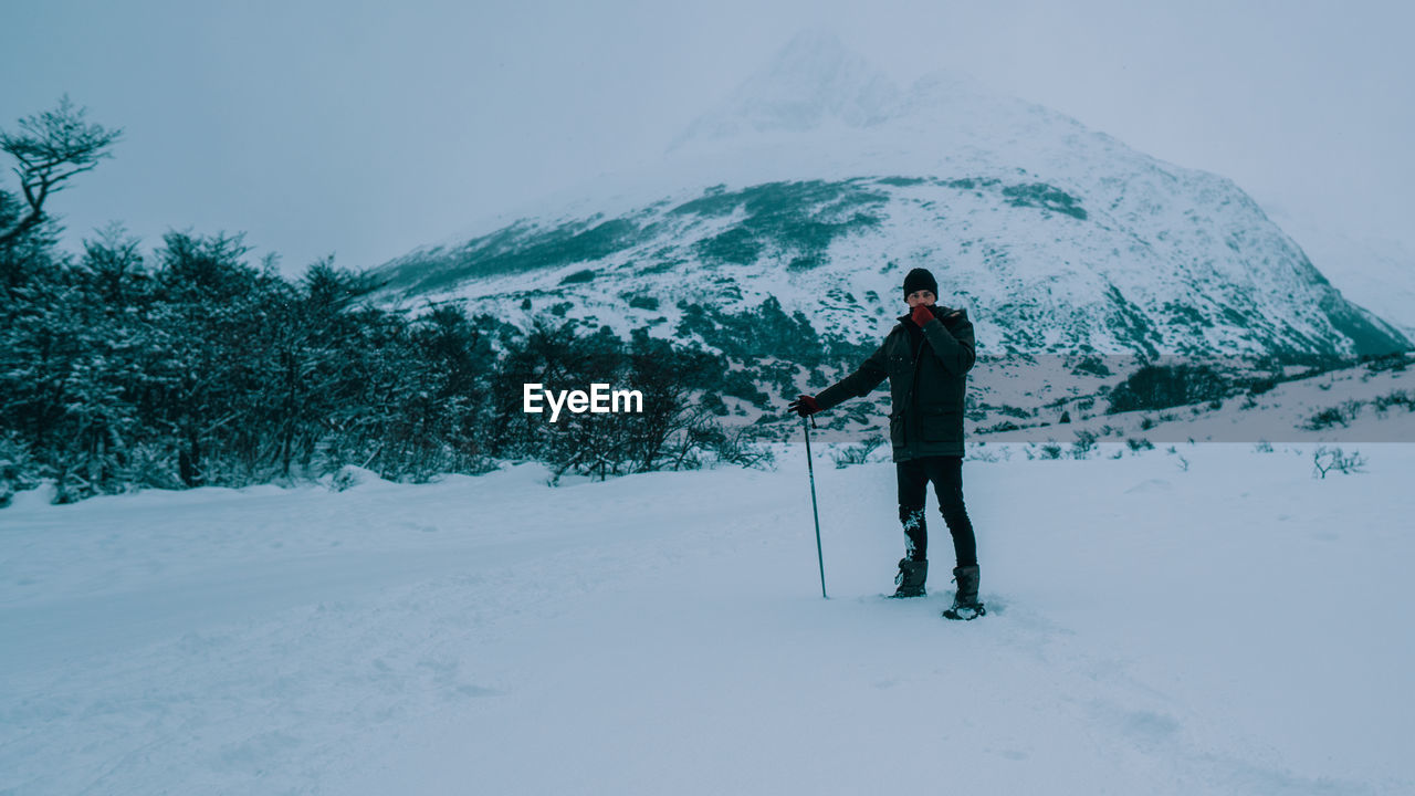 MAN STANDING ON SNOW COVERED FIELD AGAINST MOUNTAINS