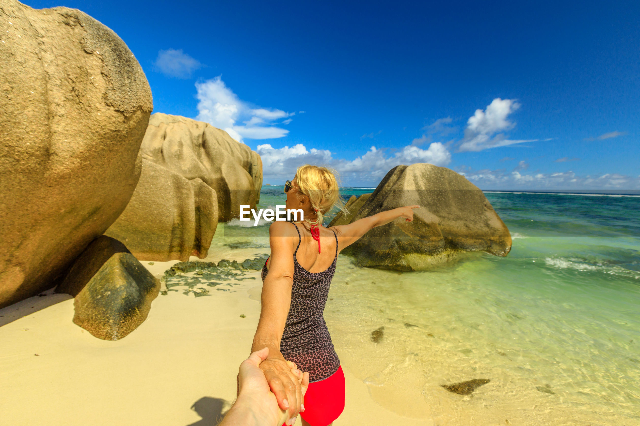 Woman holding hands while standing at beach against sky