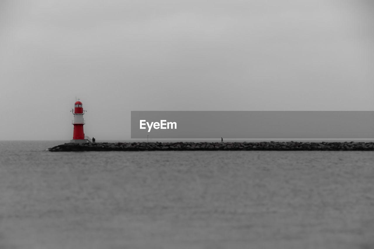 Lighthouse on groyne against sky