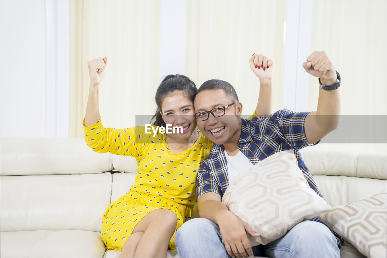 togetherness, emotion, two people, happiness, smiling, sitting, furniture, bonding, lifestyles, women, real people, casual clothing, young adult, indoors, portrait, three quarter length, leisure activity, positive emotion, young women, sofa, human arm, arms raised, couple - relationship