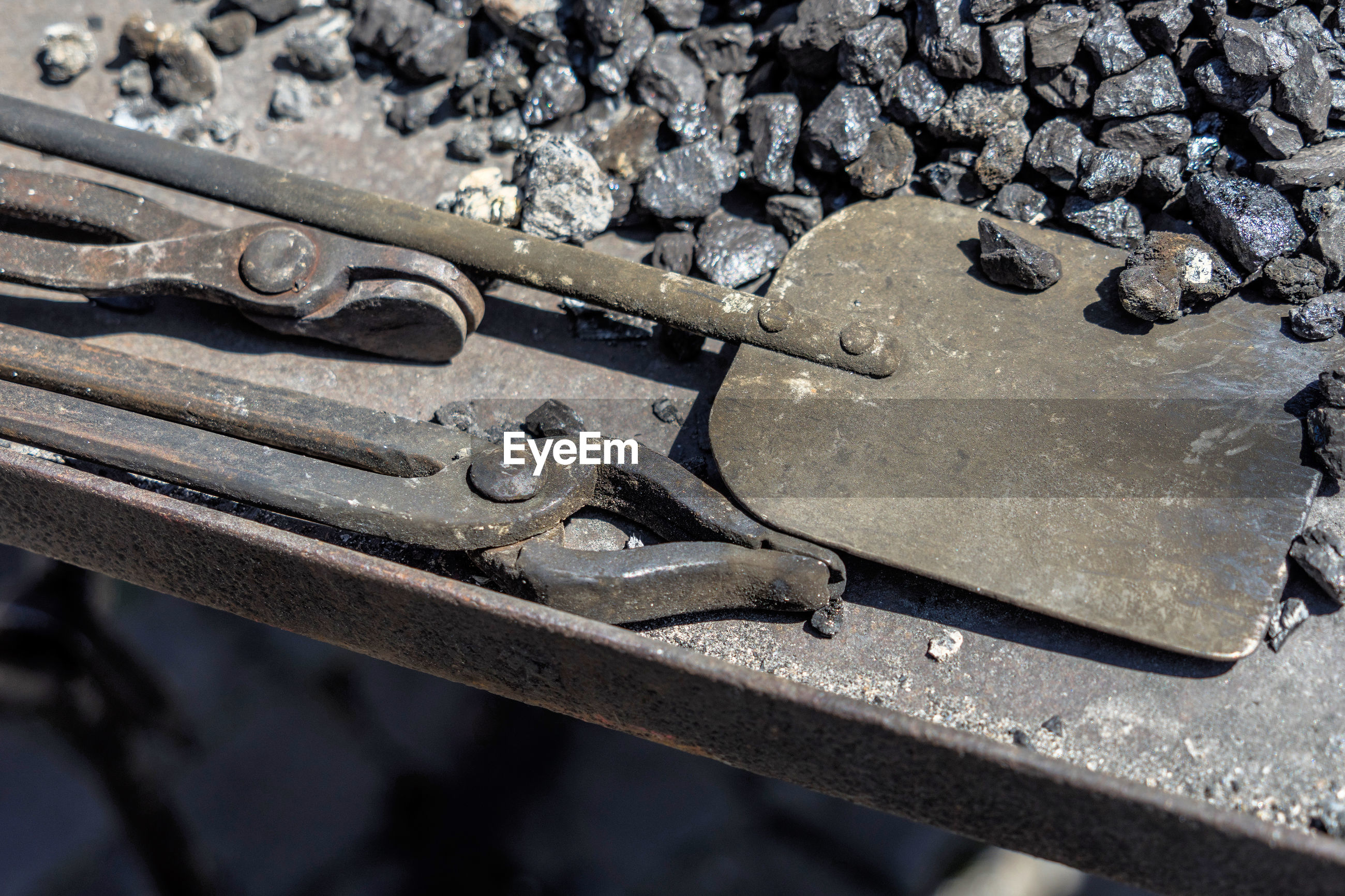 High angle view of metal work tools and stones