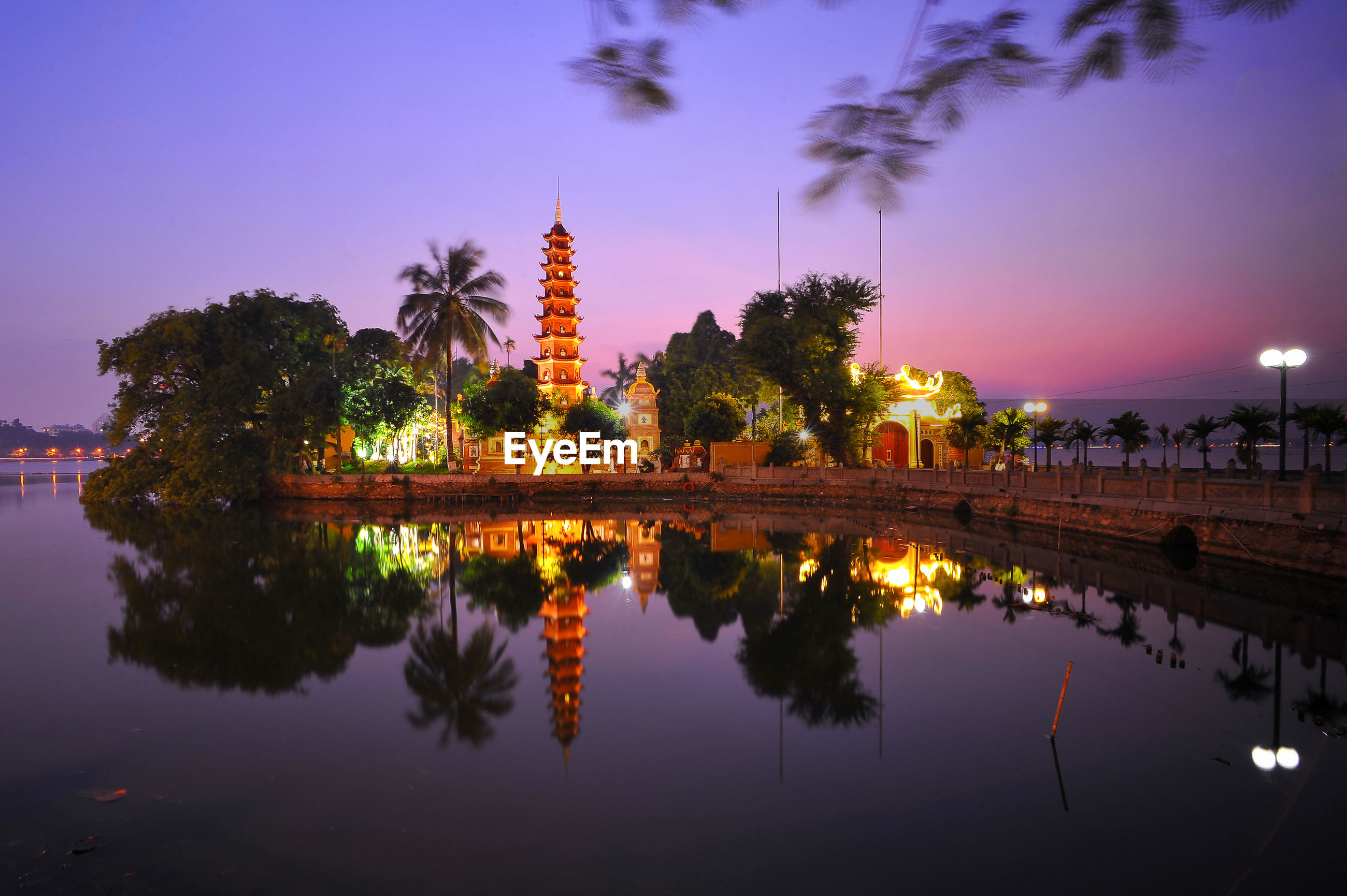 Illuminated tran quoc pagoda by reflection lake against sky