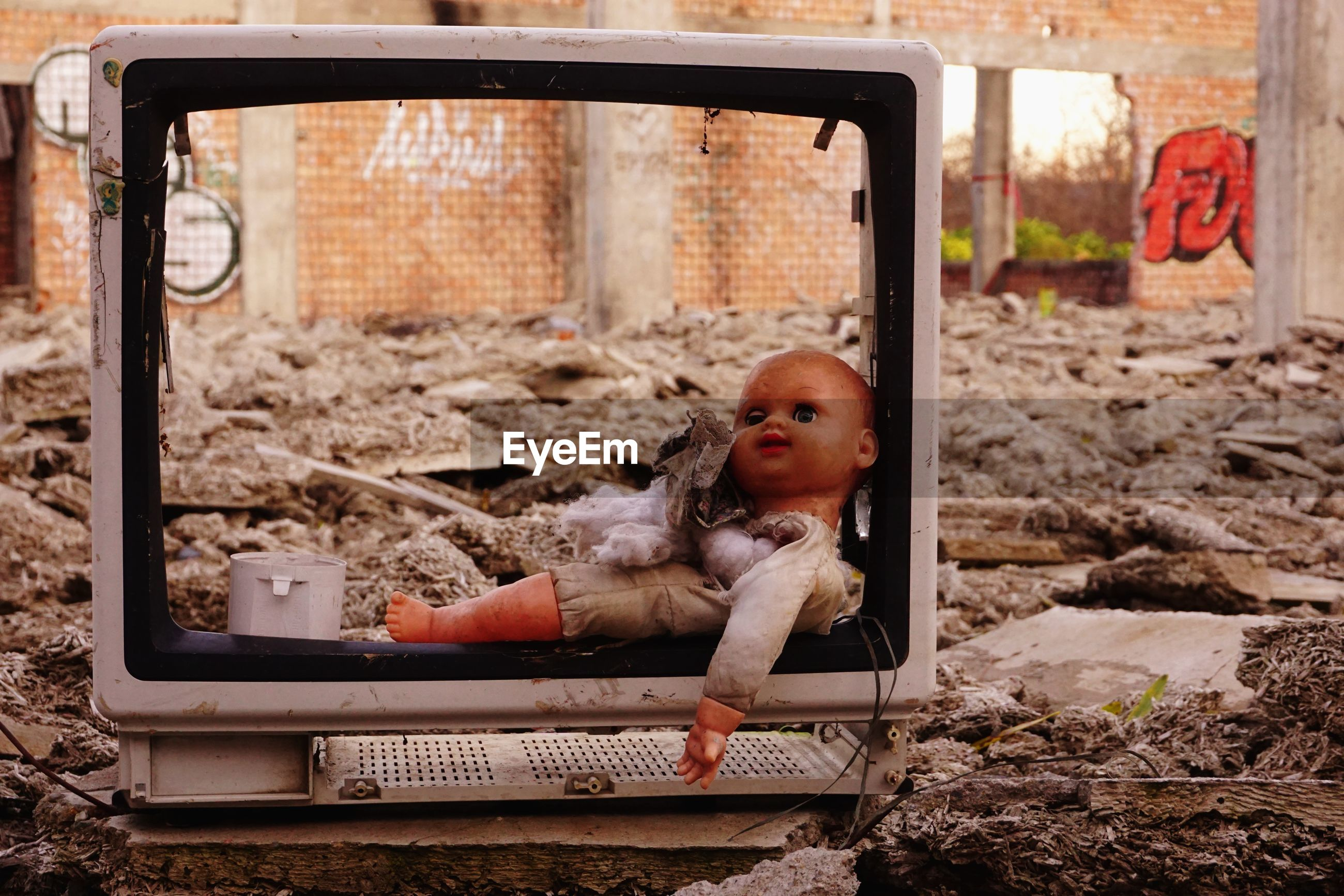 Close-up of abandoned doll and television set outdoors