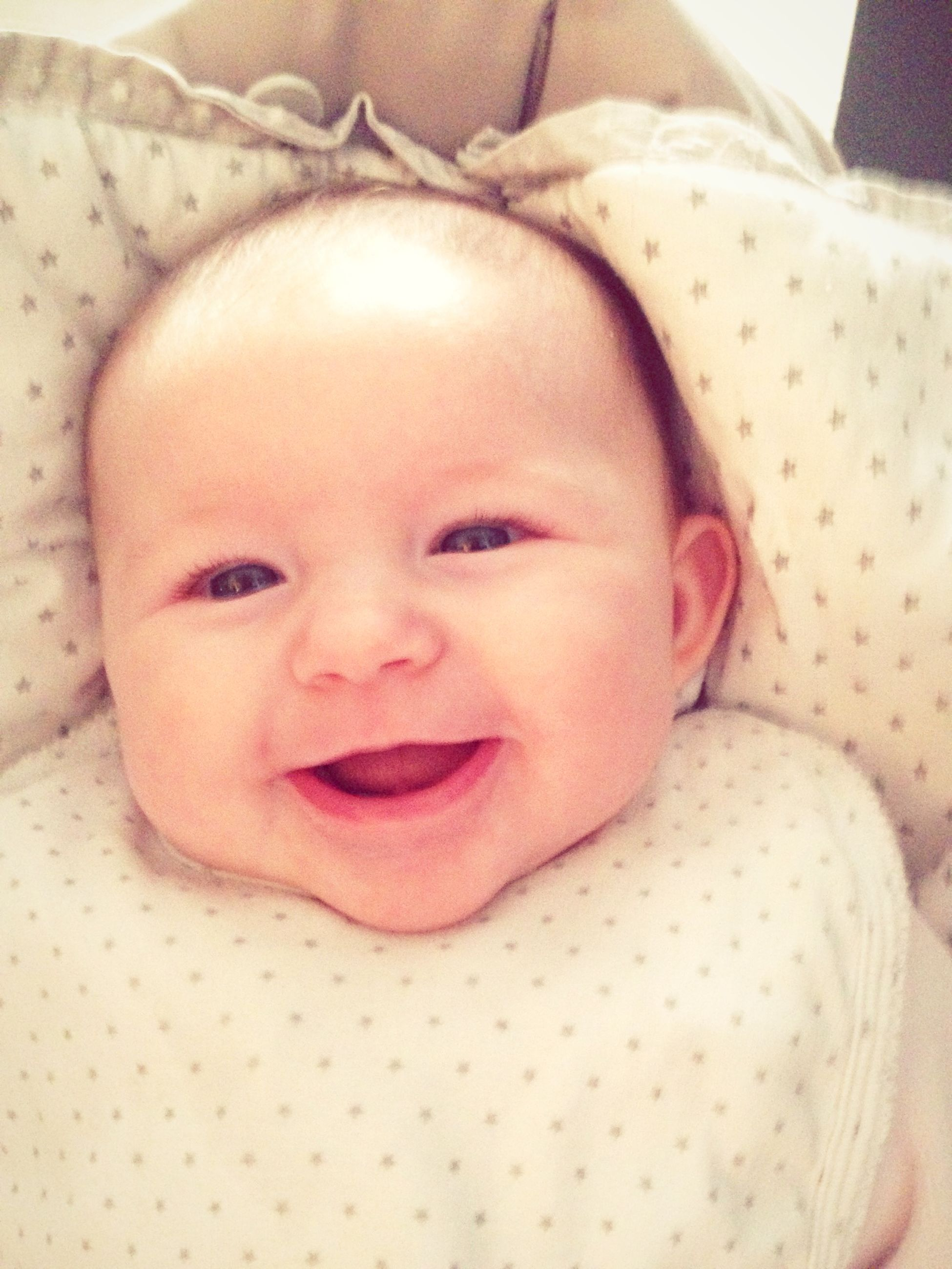 High angle portrait of smiling baby girl on bed
