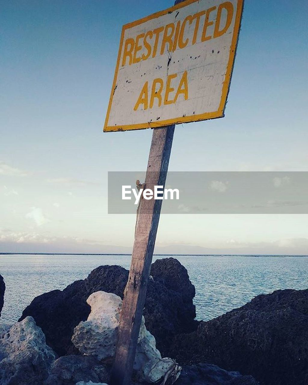 sea, water, sky, horizon, horizon over water, rock, communication, sign, solid, rock - object, text, nature, scenics - nature, tranquil scene, no people, tranquility, western script, beach, land