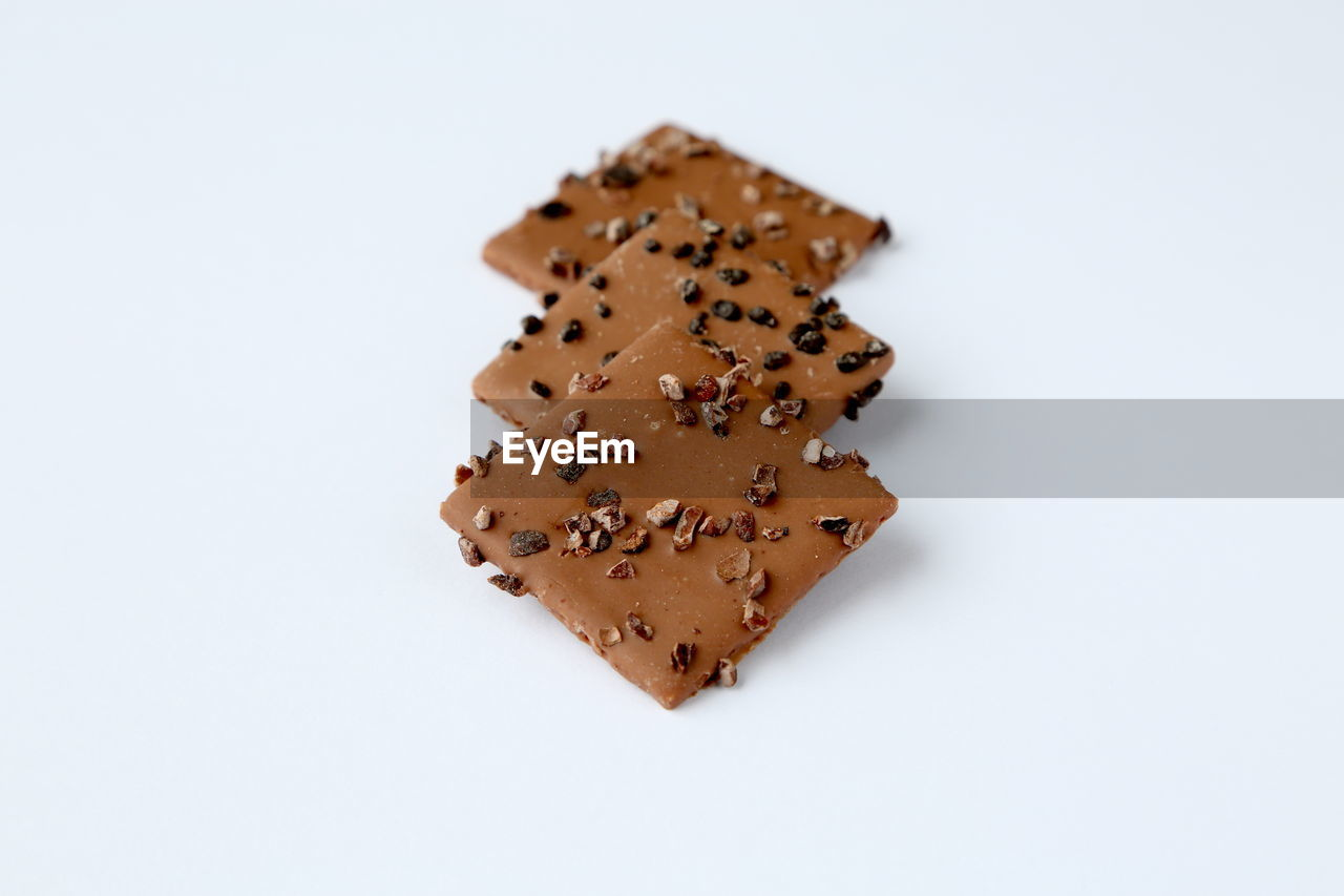 white background, studio shot, food and drink, still life, indulgence, food, high angle view, cookie, puzzle, no people, sweet food, close-up, freshness, indoors, ready-to-eat