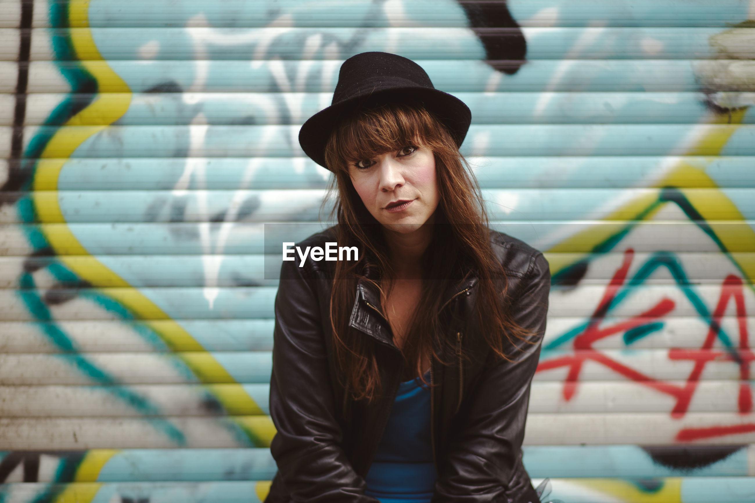 Portrait of woman wearing hat against graffiti shutter in city