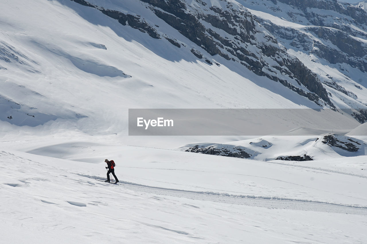 Rear View Of Person Skiing On Snowcapped Mountain