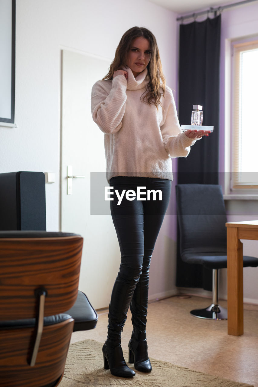 Full length portrait of woman holding drinking glass at home