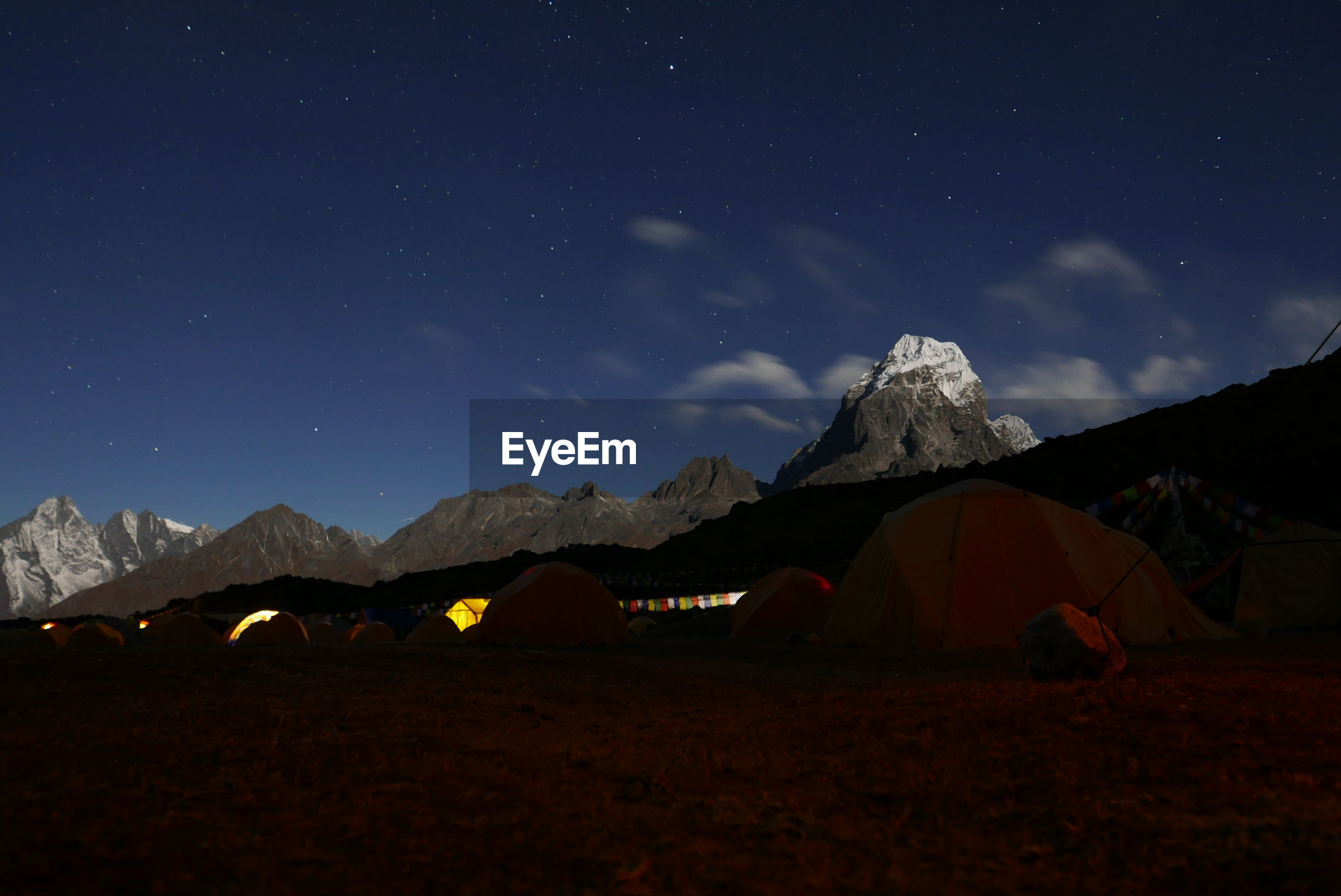 Tents by rocky mountains against sky at night
