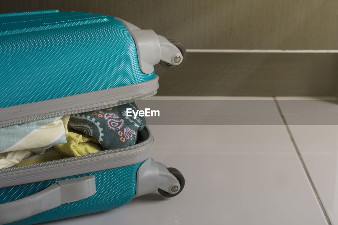 High Angle View Of Open Luggage On White Tiled Floor