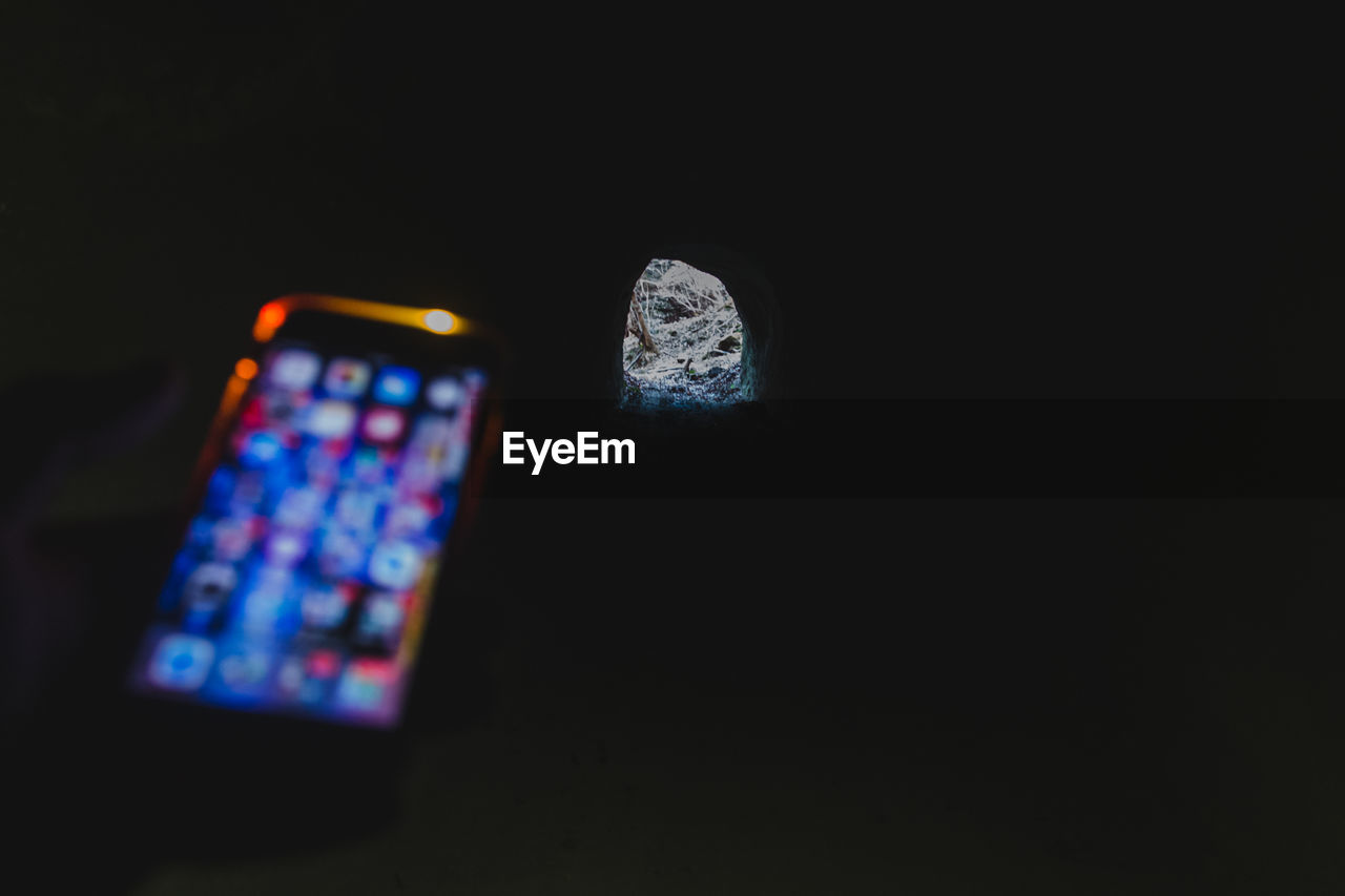 Close-Up Of Mobile Phone And Precious Gemstone On Black Background