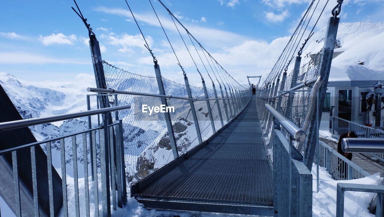 Bridge Over Snowcapped Mountains Against Sky