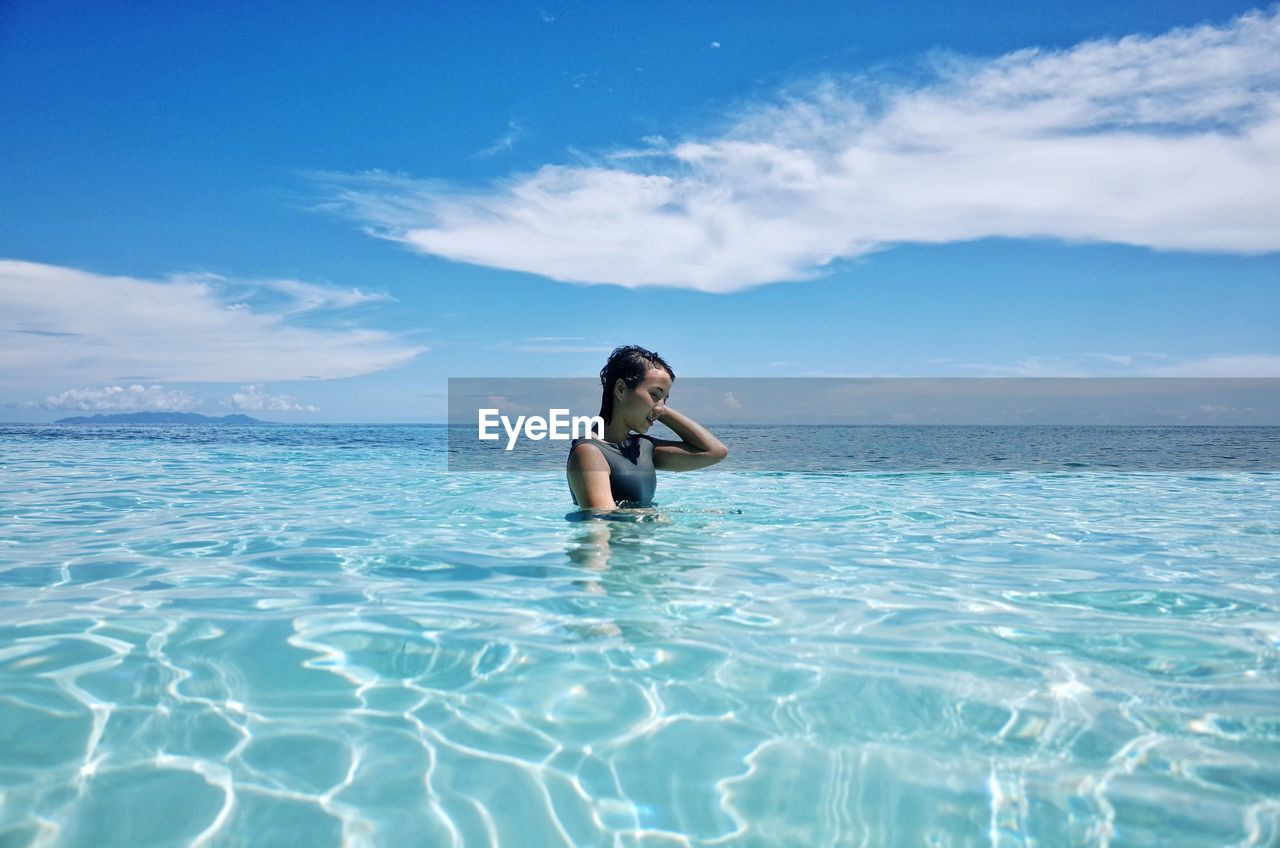 Young woman standing in sea against sky on sunny day