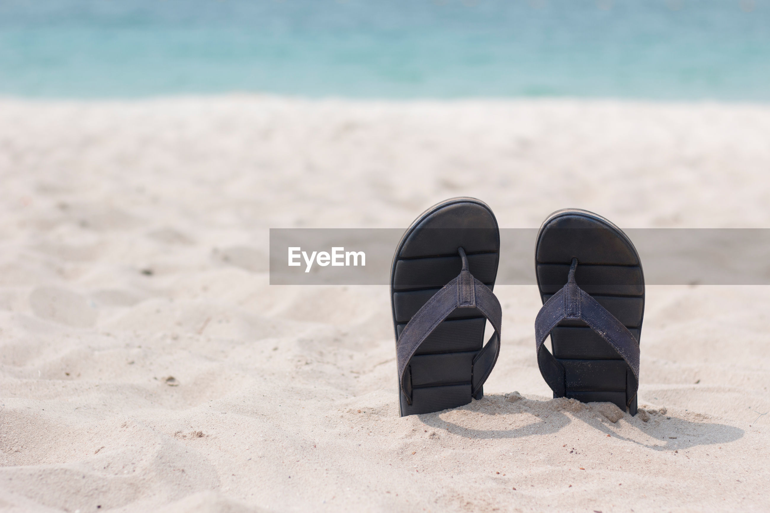 Close-up of slippers on beach