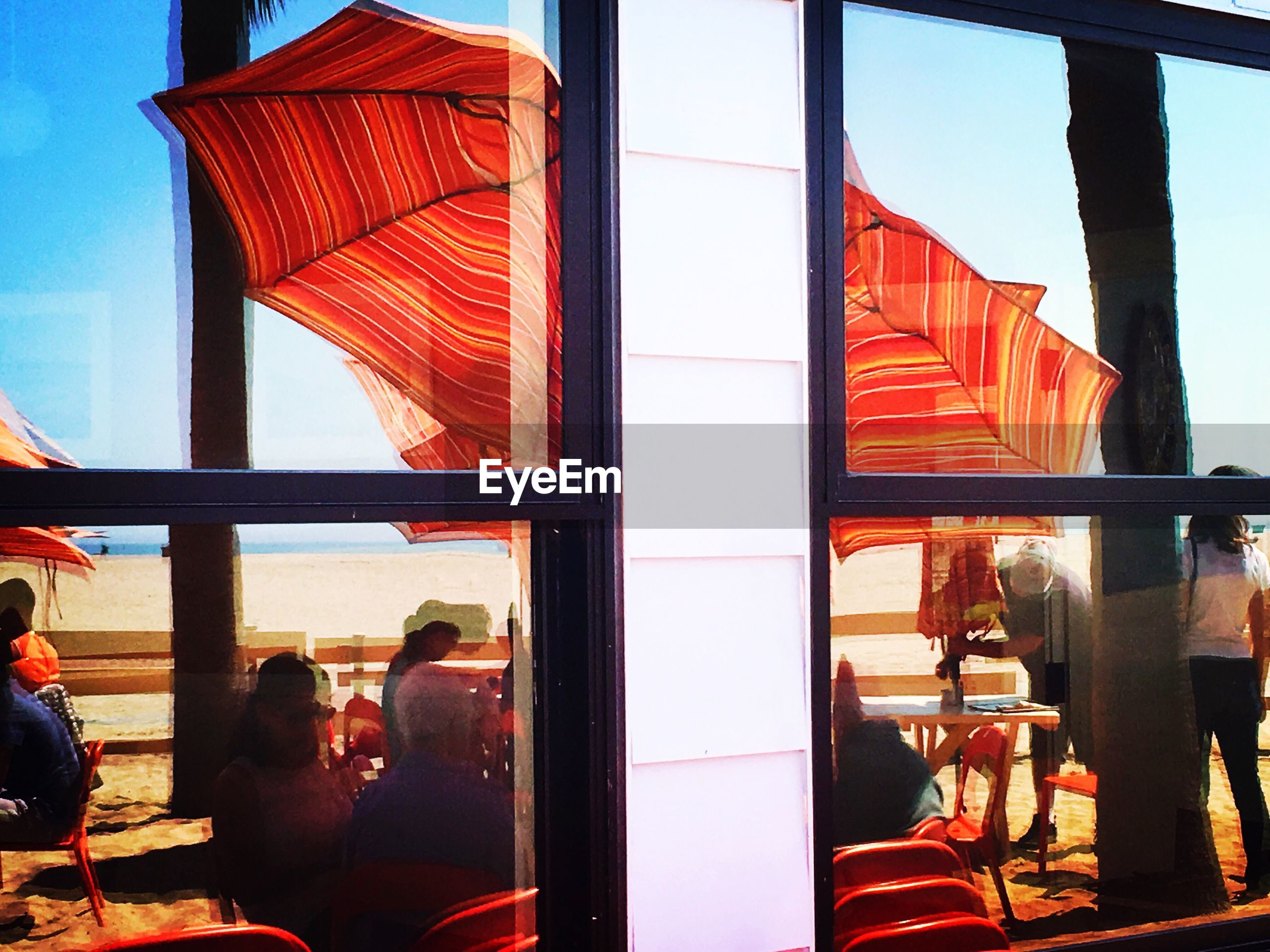 People at sidewalk cafe at shore seen through glass window