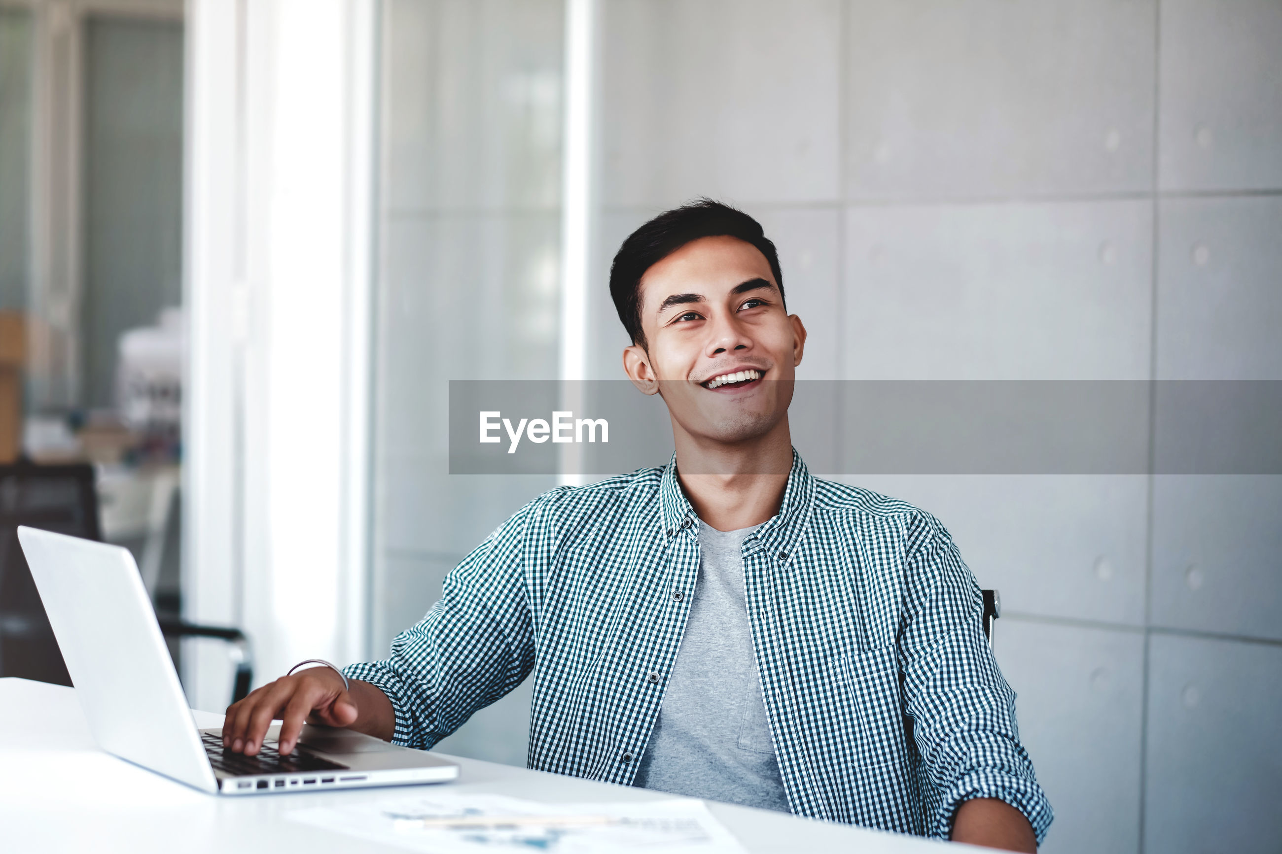 Smiling young businessman using laptop while sitting at office