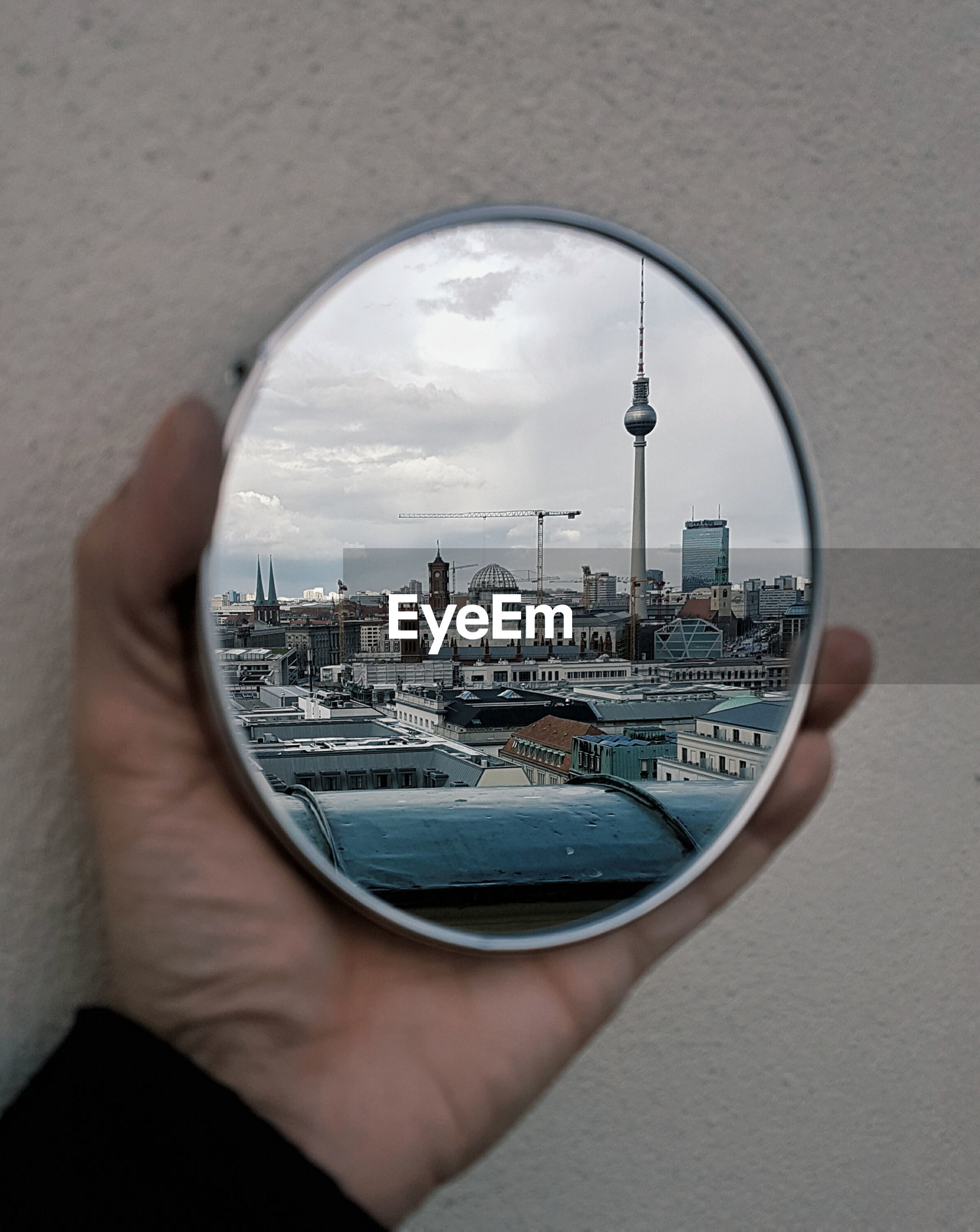 Cropped image on hand holding mirror with reflection of fernsehturm and cityscape