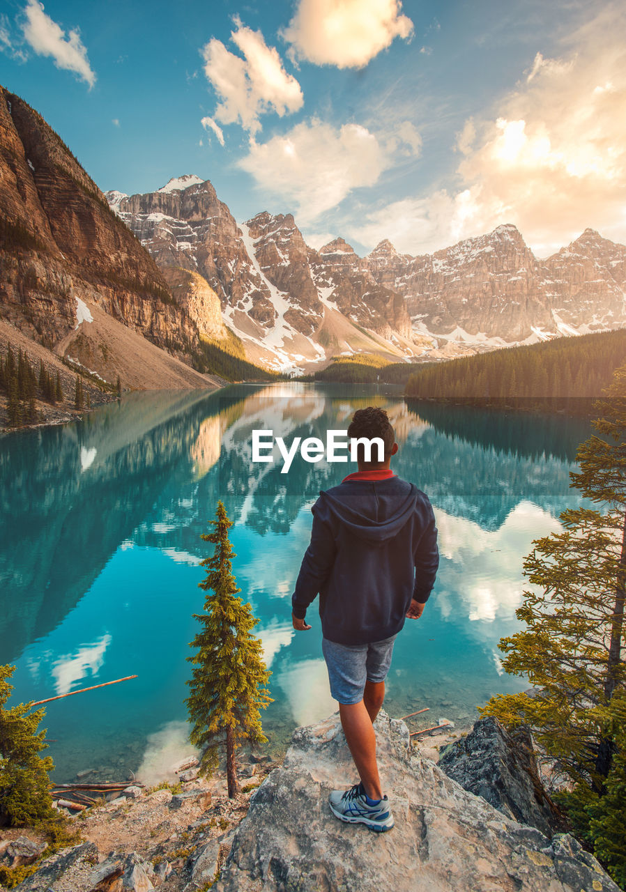 mountain, beauty in nature, nature, real people, scenics, mountain range, rear view, water, lake, one person, standing, leisure activity, rock - object, adventure, lifestyles, hiking, sky, outdoors, tranquil scene, tranquility, full length, physical geography, day, snow, landscape, cold temperature, men, people