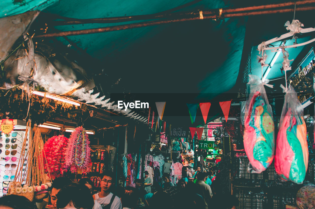 hanging, market, retail, market stall, real people, group of people, for sale, women, night, illuminated, business, shopping, lighting equipment, choice, men, small business, people, adult, variation, crowd, outdoors, sale, retail display, street market