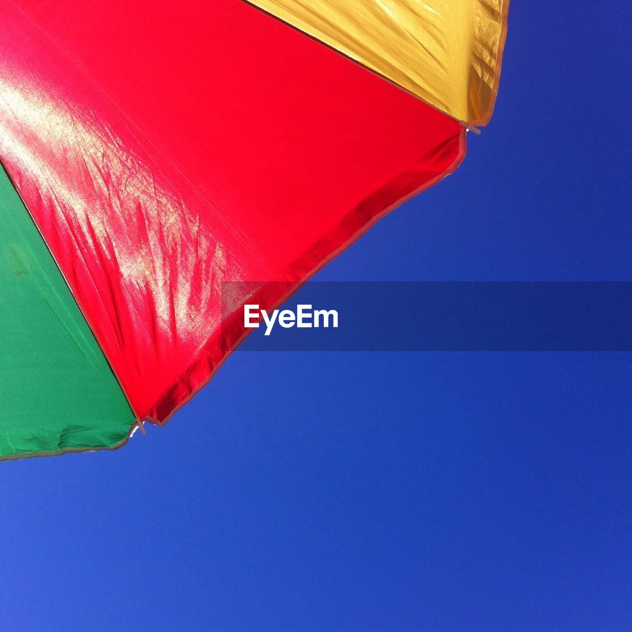 Low angle view of sunshade against clear sky