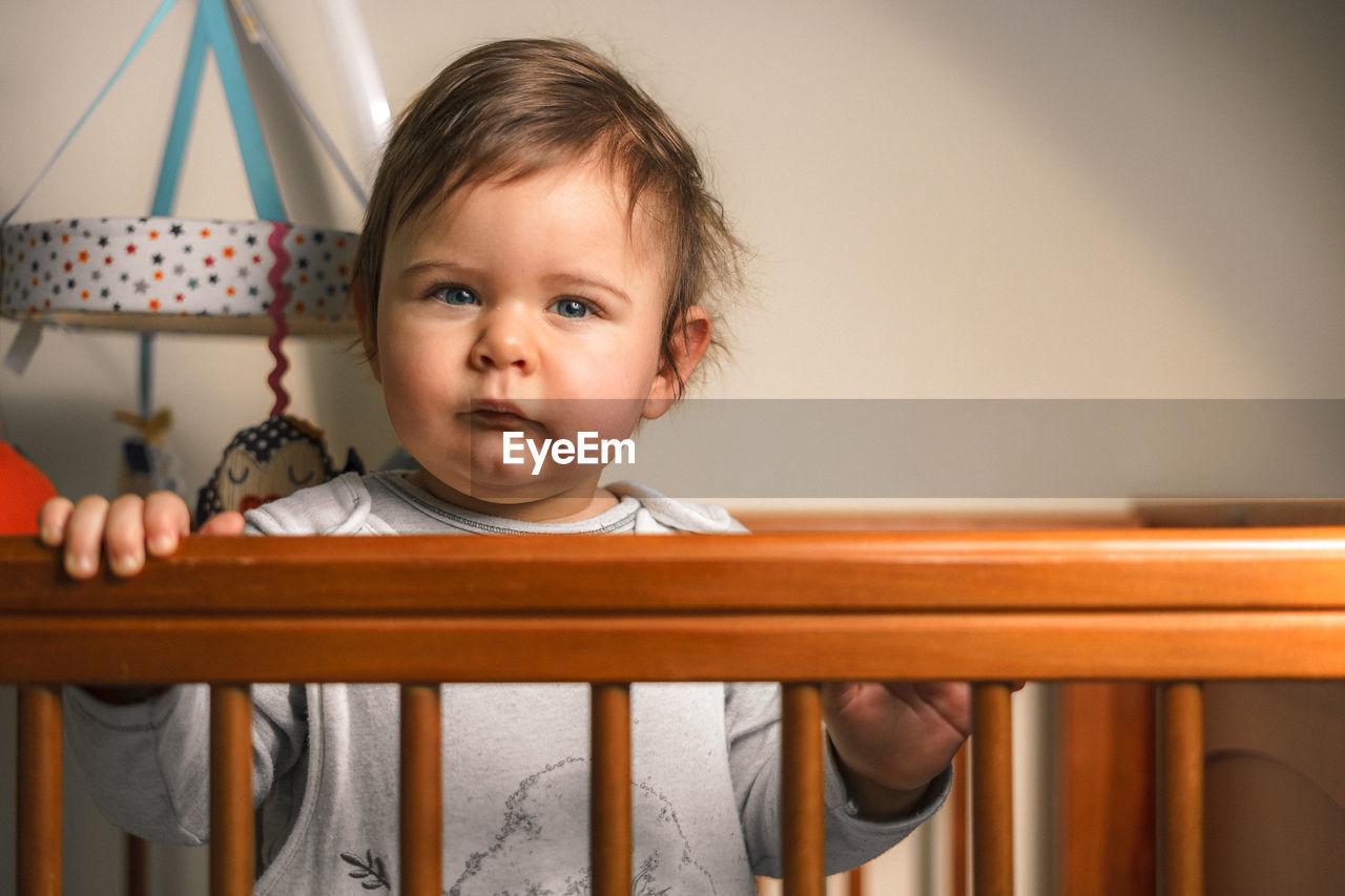 Portrait Of Cute Baby Boy In Crib