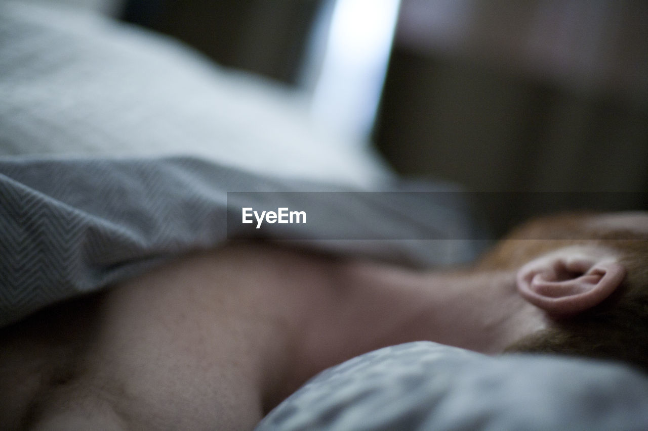Close-Up Of Man Sleeping On Bed At Home