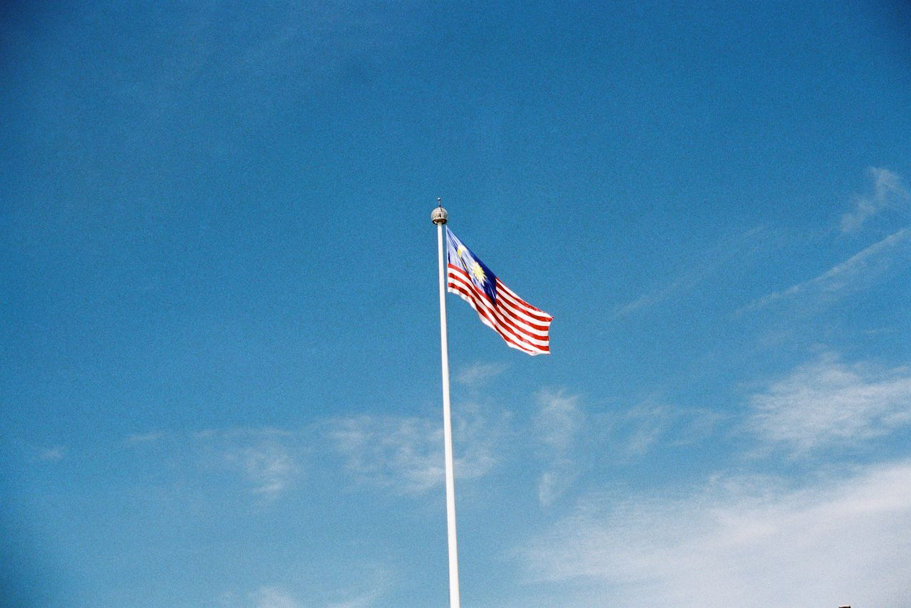 sky, low angle view, flag, patriotism, cloud - sky, blue, pole, wind, striped, day, no people, nature, environment, outdoors, waving, symbol, emotion, independence, national icon