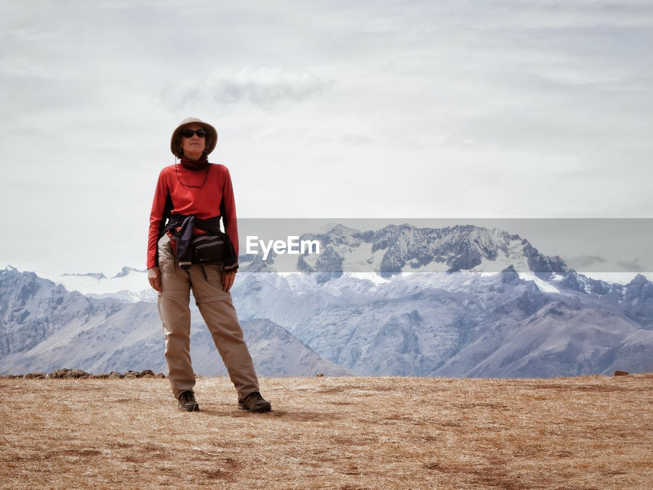 mountain, real people, scenics - nature, leisure activity, beauty in nature, one person, full length, mountain range, sky, cloud - sky, lifestyles, winter, portrait, young adult, standing, looking at camera, nature, front view, outdoors, snowcapped mountain