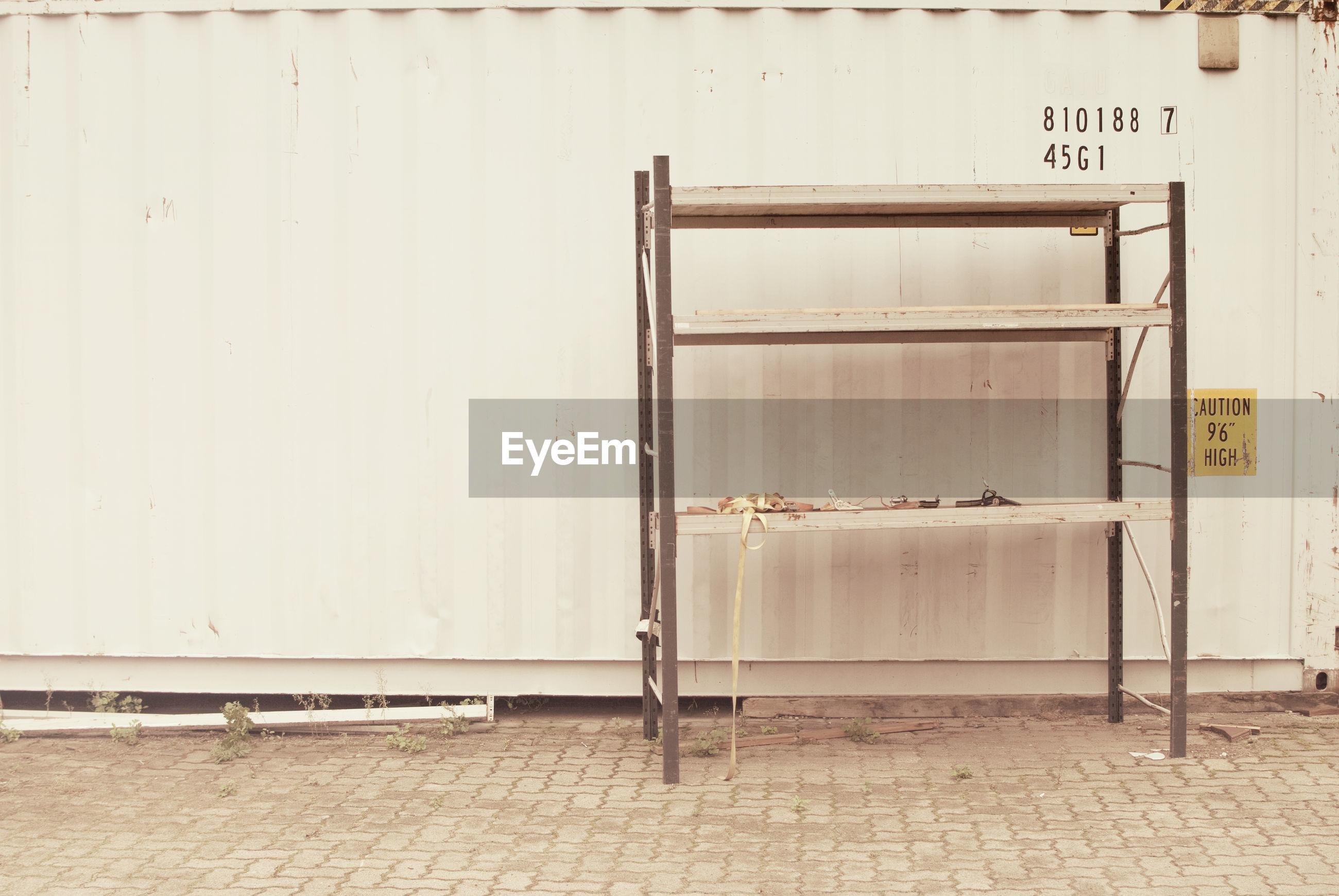 Shelf against wall on footpath
