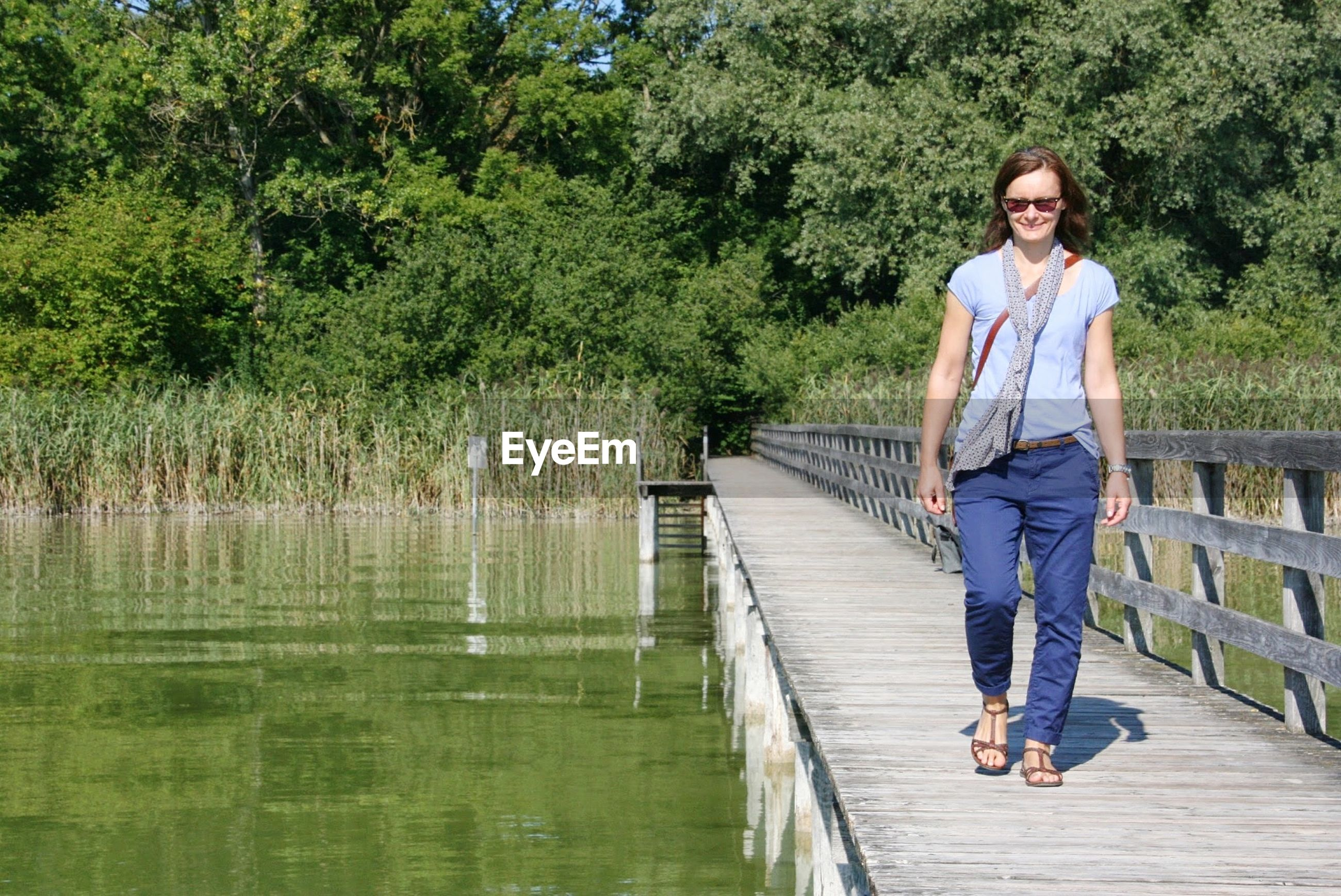 Full length of woman walking on pier over lake against trees