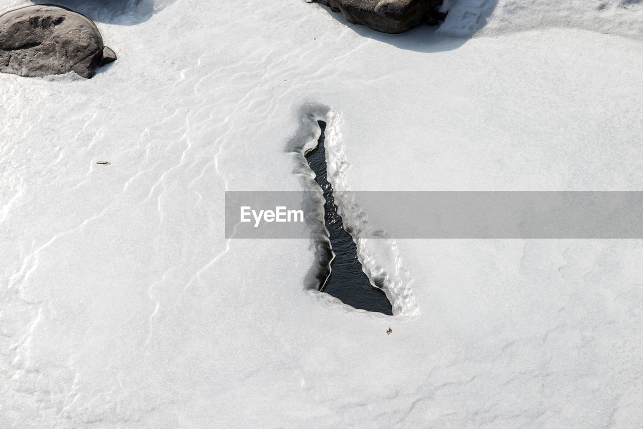 snow, winter, cold temperature, white color, day, nature, no people, high angle view, land, frozen, covering, field, beauty in nature, outdoors, tranquility, environment, footprint, ice, water, powder snow