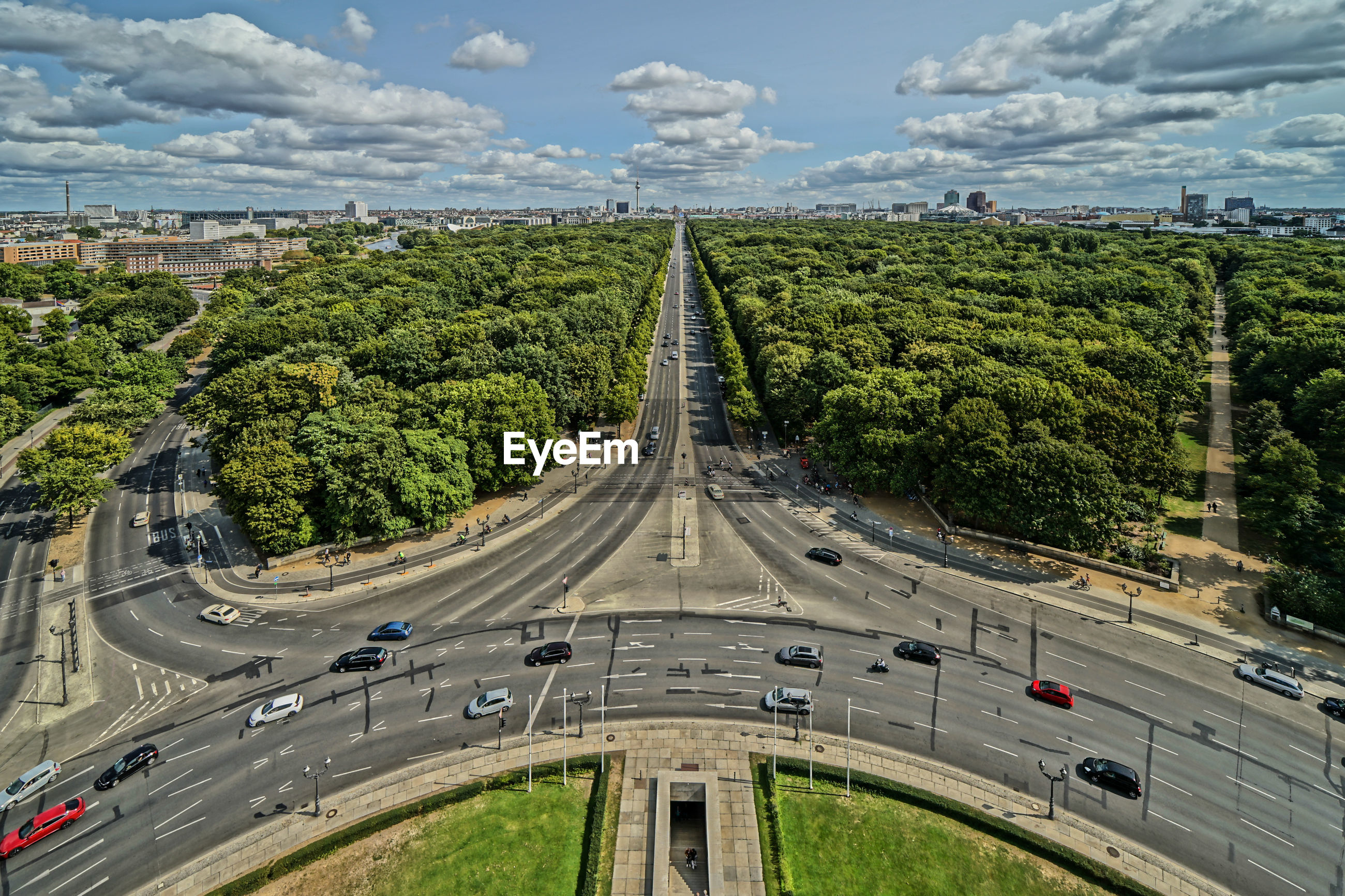 HIGH ANGLE VIEW OF ROAD AMIDST TREES AND CITY AGAINST SKY
